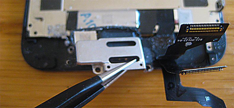 ピンセットでイヤースピーカー固定板を取り外す